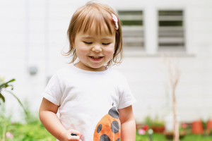 Happy toddler girl playing in her backyard