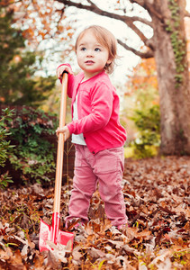 Happy toddler girl playing in the leaves in autumn