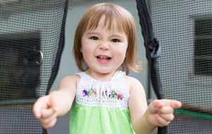 Happy toddler girl playing on her trampoline