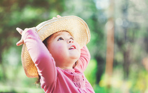 Happy toddler girl playing outside in a hat