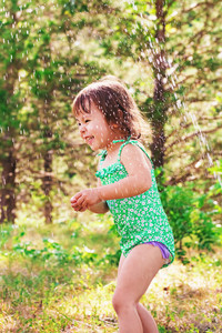 Happy toddler girl playing outside in a sprinkler