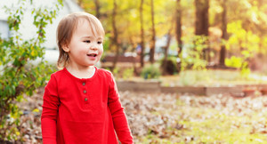 Happy toddler girl playing outside in autumn
