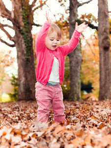 Happy toddler girl playing outside in the leaves in autumn