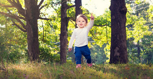 Happy toddler girl playing outside on bright summer day