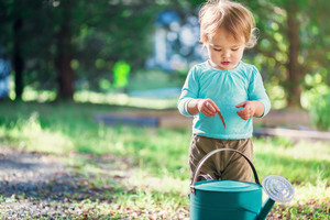 Happy toddler girl playing outside with a watering can