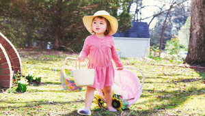 Happy toddler girl playing outside with an Easter basket