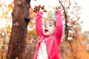 Happy Toddler girl playing outside with autumn leaves