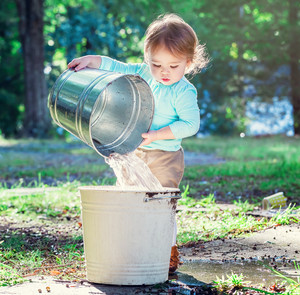 Happy toddler girl playing outside with buckets
