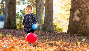 Happy toddler girl playing with balloons in the autumn leaves outside