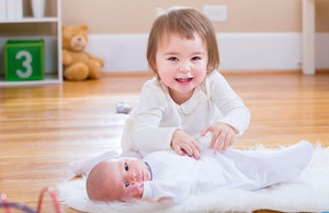 Happy toddler girl playing with her newborn baby sister