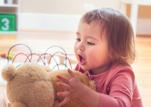 Happy toddler girl playing with her teddy bear at house
