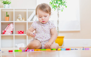 Happy toddler girl playing with her wooden toy blocks