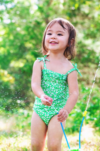 Happy toddler girl playing with sprinkler outside