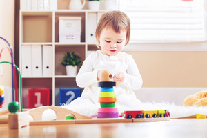 Happy toddler girl playing with toys in her house