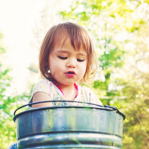 Happy toddler girl playing with watering cans and buckets outside