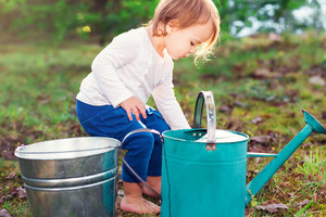 Happy toddler girl playing with watering cans outside
