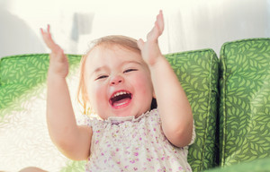Happy toddler girl smiling and clapping her hands