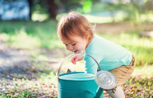 Happy toddler girl smiling and playing outside with a watering can
