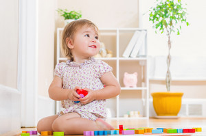 Happy toddler girl smiling and playing with her toys in her house