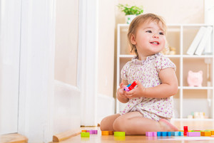 Happy toddler girl smiling and playing with her wooden toy blocks in her house