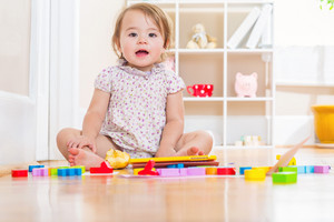 Happy toddler girl smiling and playing with toy blocks inside her house