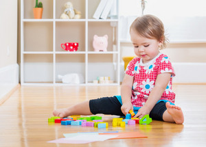 Happy toddler girl smiling and playing with wooden toy blocks inside her house