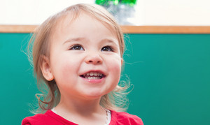 Happy toddler girl smiling in front of a green chalkboard