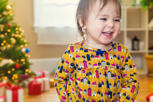 Happy toddler girl smiling in front of her Christmas tree and presents