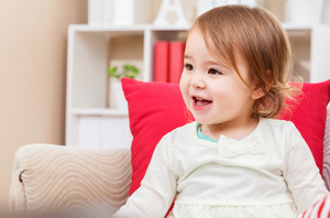 Happy toddler girl smiling in her living room