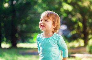 Happy toddler girl smiling outside on a sunny afternoon