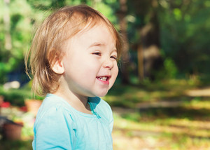 Happy toddler girl smiling outside on a sunny day