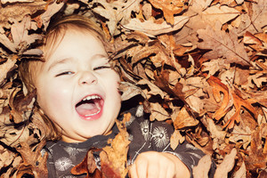 Happy toddler girl smiling while lying down in big pile of leaves