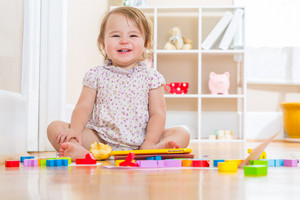Happy toddler girl smiling while playing with her toy blocks