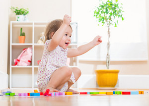 Happy toddler girl smiling while playing with her wooden toy blocks
