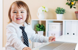 Happy toddler girl smiling while using her laptop