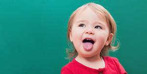 Happy toddler girl sticking her tongue out in front of a green chalkboard