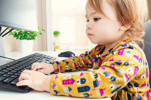 Happy toddler girl typing on her computer keyboard at home