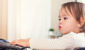 Happy toddler girl typing on her computer keyboard