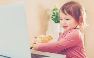 Happy toddler girl using a laptop with her teddy bear