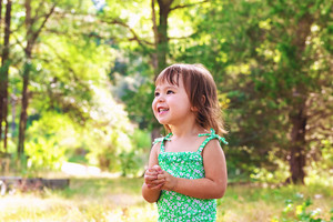 Happy toddler girl wearing bathing suit playing outside