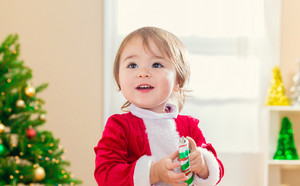 Happy toddler girl with a big smile in front of her Christmas tree