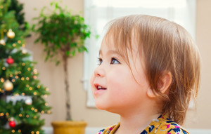 Happy toddler girl with a nice smile in front of her Christmas tree