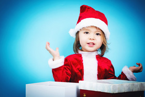 Happy toddler girl with a Santa hat with Christmas presents