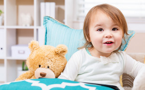 Happy toddler girl with her teddy bear and tablet computer