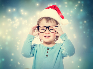 Happy toddler girl with Santa hat wearing glasses