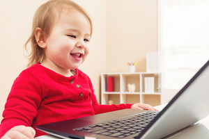 Happy toddler girl working on her laptop