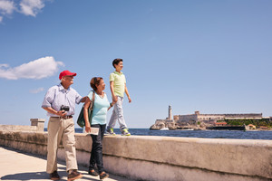 Happy tourists on holidays in Havana, Cuba. Hispanic family with grandpa, grandma and grandson traveling and walking together on the Malecon