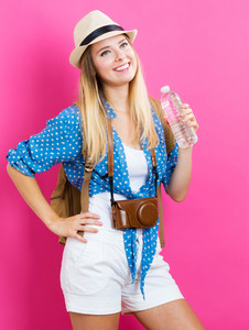 Happy Traveling woman with a water bottle on a pink background