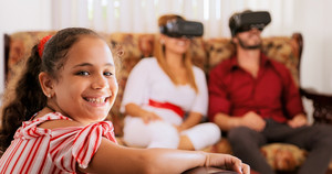 Happy white family at home. Hispanic father, mother and child playing with virtual reality goggles. Portrait of girl smiling at camera.