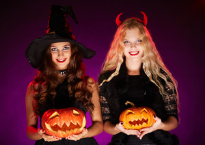 Happy witches with pumpkins looking at camera